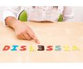 """immagine raffigurante una mano che indica la parola """"dislessia"""" scritta con la lettera """"e"""" capovolta"""