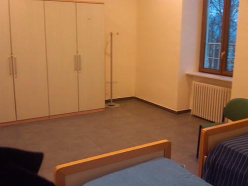 camera spaziosa con armadio e finestra sul fondo