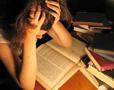 immagine di una studentessa che legge un volume con le mani nei capelli, circondata da tanti libri
