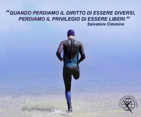 """Il nuotatore paraolimpico, Salvatore Cimmino, si incammina verso il mare con in alto la scritta """"quando perdiamo il diritto di essere diversi, perdiamo il privilegio di essere liberi""""."""