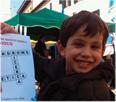 foto raffigurante un bambino con sindrome di X fragile sorridente e con un mano un cruciverba con parole relative al tema X fragile