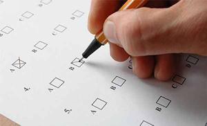 """immagine raffigurante un test a risposta multipla con una mano che traccia una """"x"""" su una risposta"""