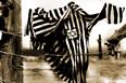 Foto d'epoca raffigurante giacca di prigioniero, a righe bianche e nere e con stella di David, appesa al filo spinato del campo di prigionia