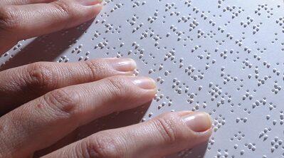 Immagine di mani che leggono il braille