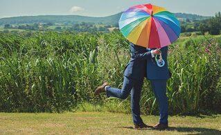 Coppia omosessuale sotto un ombrello rainbow