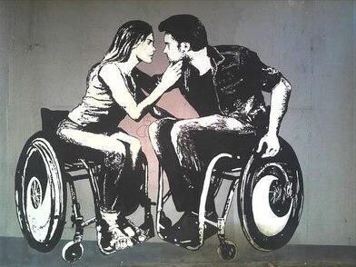 Ragazza e ragazzo seduti sulla sedia a ruote che si guardano negli occhi.
