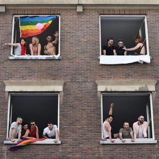 Persone affacciate alla finestra con bandiere rainbow