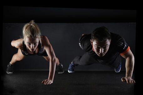 Immagine di una persona maschile accanto a una femminile che gareggiano a una corsa