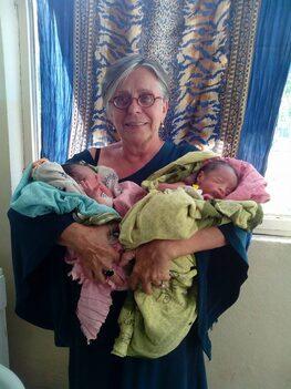 L'immagine ritrae la Dott.ssa Bertolazzi che ha in braccio due bambini africani appena nati