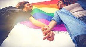 Due donne che si tengono per mano con dietro le spalle una bandiera rainbow