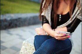 Donna seduta col cellulare